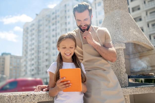 Папа и дочь смотрят что-то на планшете
