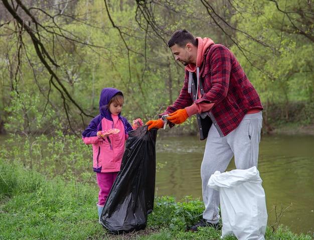 Папа с дочкой мешками для мусора убирают окружающую среду от мусора.