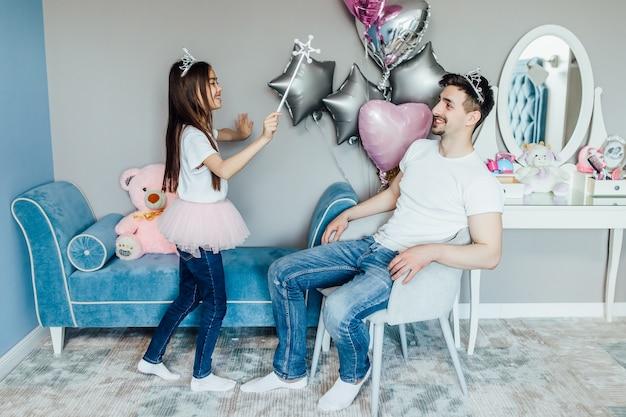 お父さんと彼の娘は一緒に遊んで楽しんでいます
