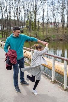 이른 봄에 도시 공원에서 산책하는 동안 아빠와 그의 어린 딸이 춤을 춘다.