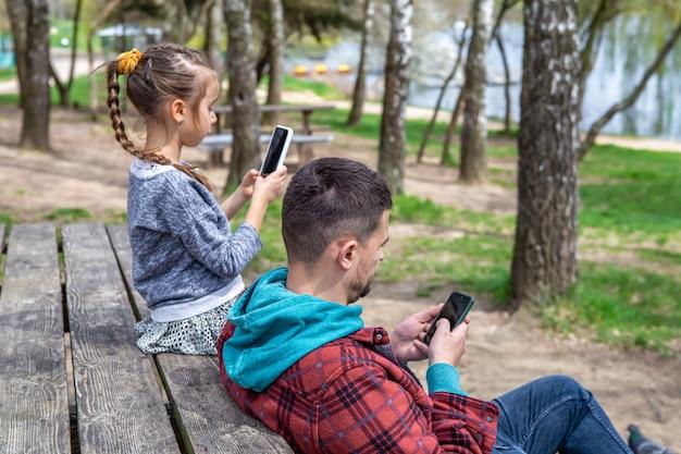 휴대 전화를 손에 들고있는 아빠와 어린 딸은 서로에게주의를 기울이지 않습니다.