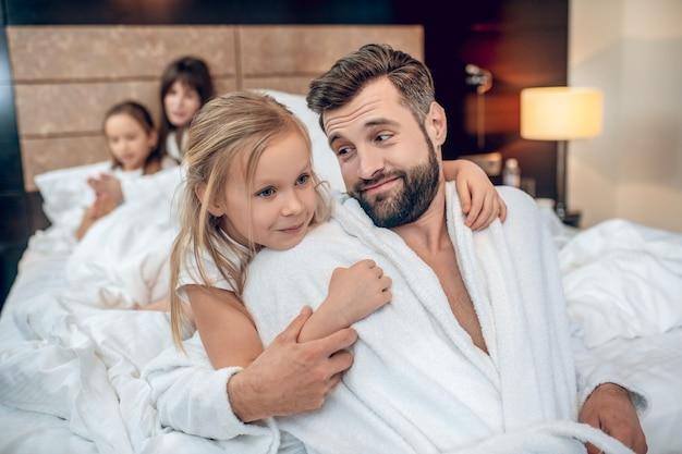 Папа и ребенок. милая блондинка обнимает своего молодого бородатого папу