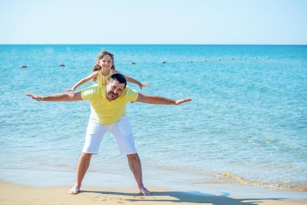 Папа и маленькая девочка играют, бегают по пляжу и дурачатся на берегу моря. семейный отдых на море с ребенком.