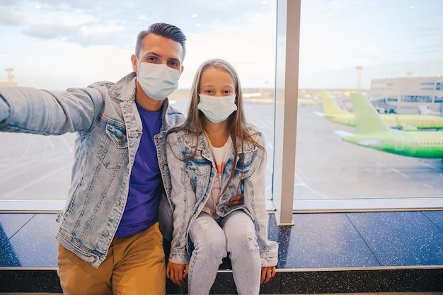 Папа и маленькая девочка с медицинскими масками в аэропорту.