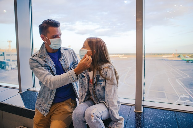 Папа и маленькая девочка с медицинскими масками в аэропорту. Premium Фотографии