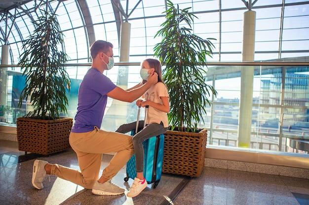 Папа и маленькая девочка в медицинских масках в аэропорту. защита от коронавируса Premium Фотографии