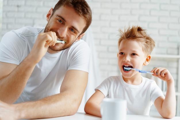 お父さんと幼い息子がバスルームで一緒に歯を磨く
