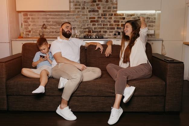 저녁에 아들이 핸드폰으로 게임을하는 동안 아빠와 엄마는 소파에서 tv를 즐기고 있습니다. 집에서 친척.