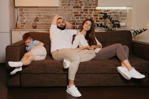아빠와 엄마는 아들이 저녁에 근처에서 자고있는 동안 소파에서 tv를보고 있습니다. 집에서 가족.