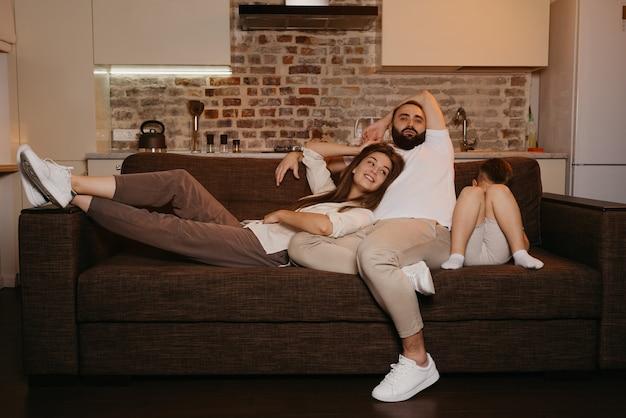 아빠와 엄마는 아들이 저녁에 근처에서 자고있는 동안 소파에서 tv를보고 있습니다. 집에서 친척.