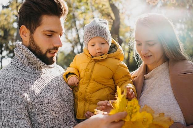外で赤ちゃんを持つお父さんとお母さん