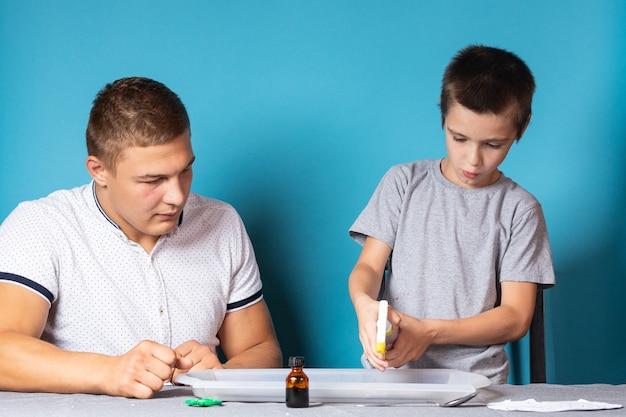 Папа и сын проводят химические опыты, наблюдая за изменением окраски хамелеона в результате химической реакции йода и крахмала в домашних условиях. мальчик распыляет йод на рисунок