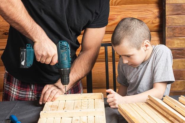 아버지와 아들이 워크숍의 테이블 위에 드라이버, 도구 및 빔을 사용하여 나무 판자를 뚫고 있습니다.