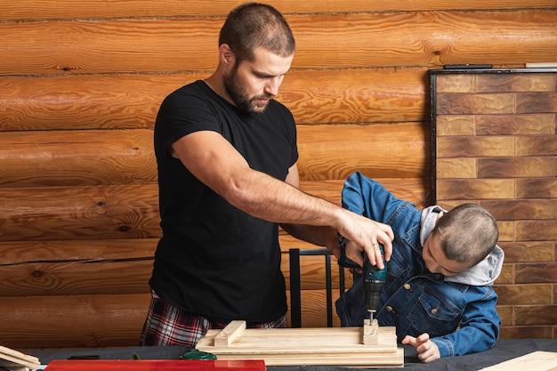お父さんと息子は、ワークショップのテーブルにドライバー、ツール、ビームを使用して木の板を掘削しています