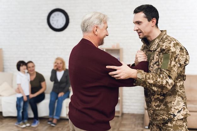 お父さんと息子は軍の後でお互いに会えてうれしいです。