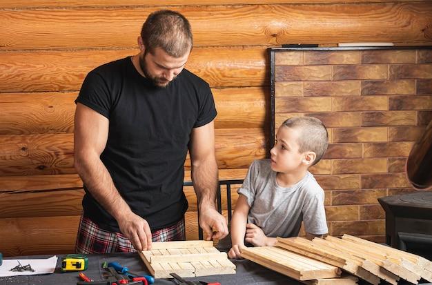 Папа и сын работают над деревянным изделием, делают разметку для крепления, инструментов и древесины на столе в мастерской.