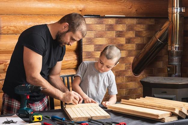 Папа и сын работают над деревянным изделием, делают разметку для крепления