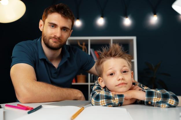 テーブルに座って一緒に学校の宿題をしているお父さんと息子