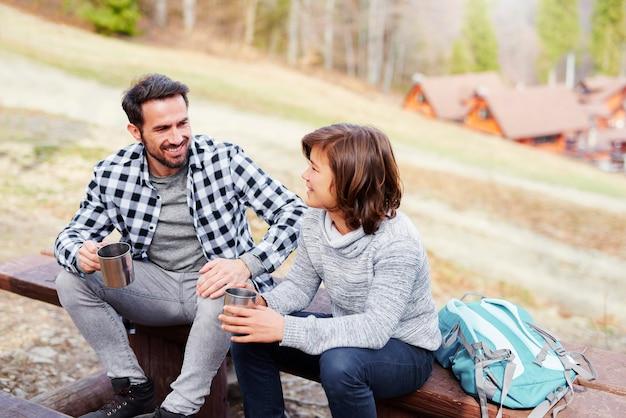 お父さんと息子はお茶を飲み、木製のベンチに座っています