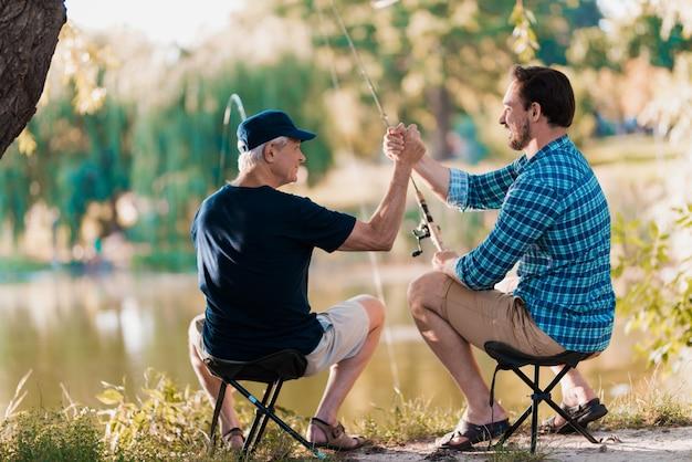 Папа и сын дают пять друг другу в природе.