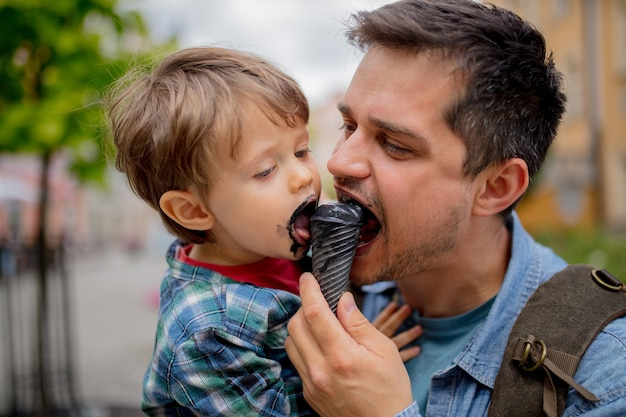 Папа и сын веселятся с черным мороженым на открытом воздухе
