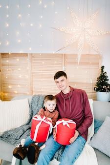 Папа и сын держат подарки на диване возле елки с рождеством христовым