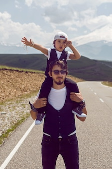 에베레스트 산의 배경에 대해 아스팔트 도로를 걷고있는 검은 조끼와 모자에 아빠와 아들