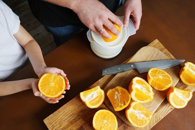 お父さんと息子は新鮮なオレンジからオレンジジュースを絞ります