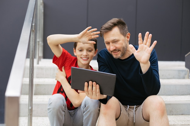 お父さんと息子は、コンクリートの階段で市内のタブレットを使用してビデオ通話を行います