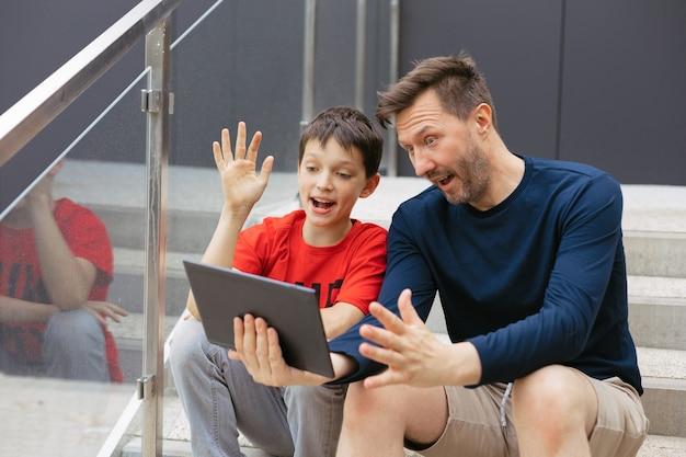 お父さんと息子は、コンクリートの階段、オンライン通信の概念、ブログで街のタブレットを使用してビデオ通話を行います