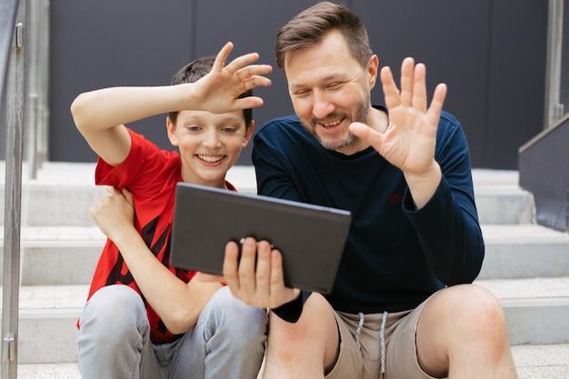 お父さんと息子がコンクリートの階段で街のタブレットを使ってビデオ通話をし、元気に手を振って挨拶します
