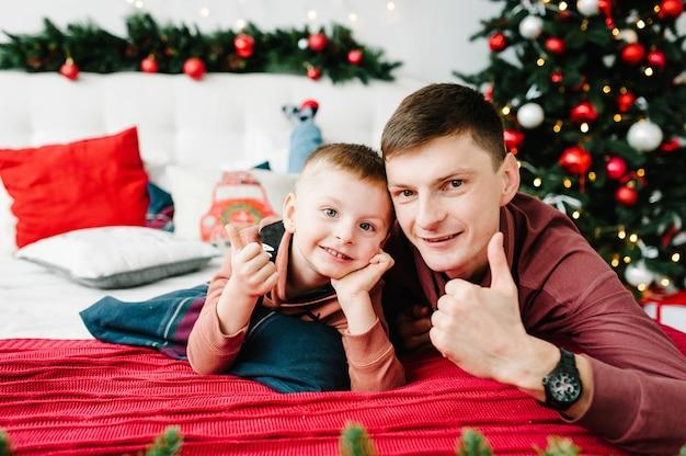 Папа и сын на кровати возле елки новый год и рождество украшенный интерьер
