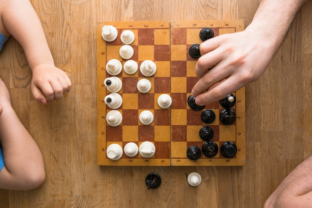 Папа и сын играют в шахматы вместе дома. вид сверху