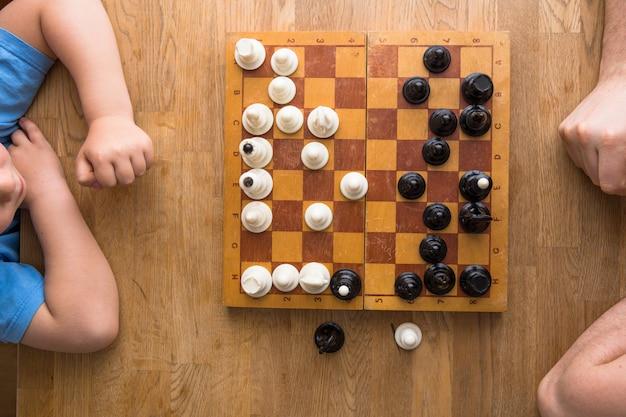 お父さんと息子が家で一緒にチェスをする