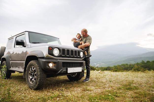 도로 여행에서 자동차 후드에서 노는 아빠와 아들