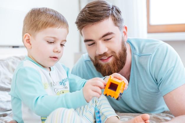 Папа и сын играют с игрушками на кровати дома