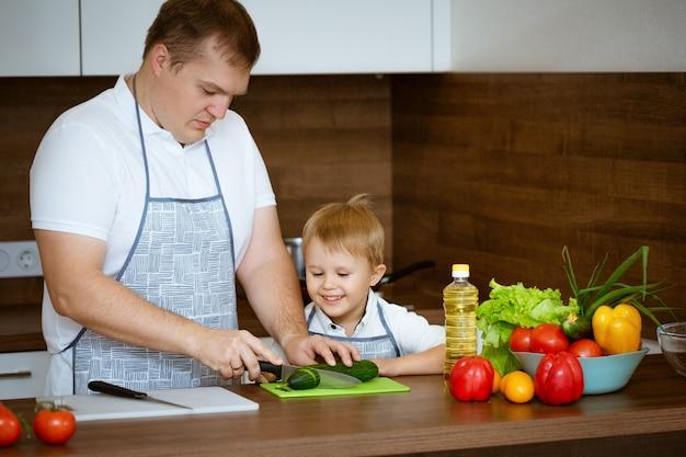 お父さんと息子のキッチンでサラダを準備して、家族料理の概念