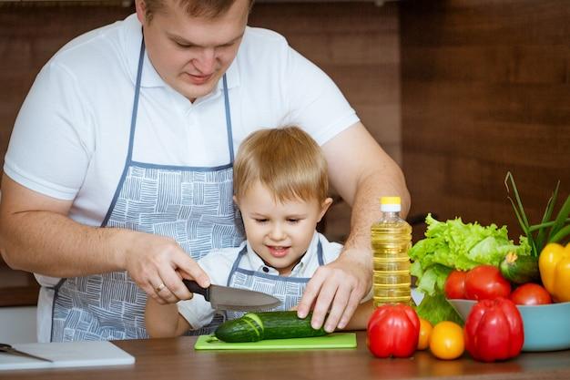 お父さんと息子が台所で家族の料理のコンセプトであるサラダを準備します。