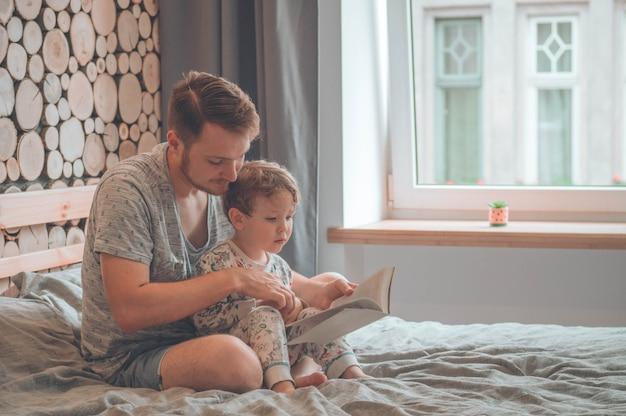 お父さんと息子が一緒に本を読んで、笑顔で抱きしめる