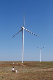 お父さんと息子はクリミア半島の夏に畑に立っている電気風車のグループの隣に立っています