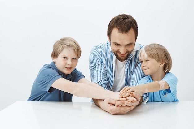 Папа и сыновья не только семья, но и коллектив. портрет счастливых красивых братьев и сестер и отца, держащихся за руки, сидя за столом и широко улыбаясь
