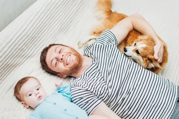 Dad and baby lying on the bed with a dog