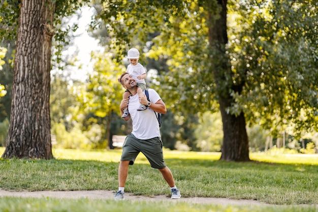 Папа несет сына на спине, и у них выходной. игра с детьми, время для отца и сына, семейный активный уик-энд. отец и сын гуляют по лесу в солнечный день