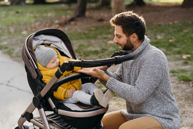 Dad and child in stroller outdoors in nature