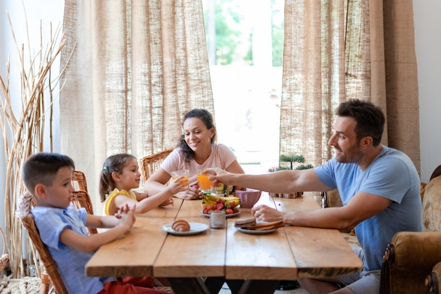 Dad and daughter are clinking glasses of fruit juice during the family breakfast