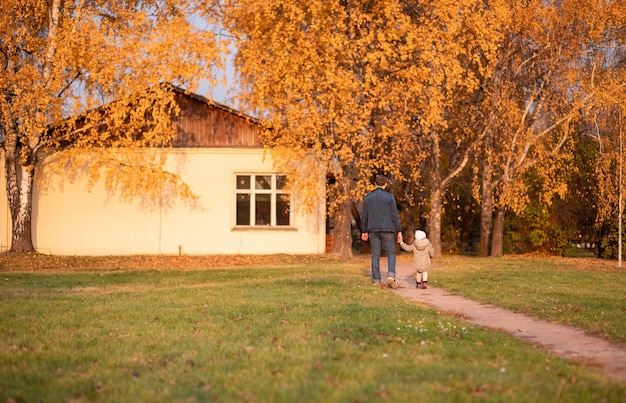 Dad and daughter are walking along the path against the background of a yellow tree in the park.