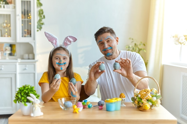 Dad and daughter faces stained with blue paint for painting eggs. on the table is a basket with easter eggs and paints.