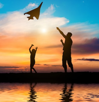 Dad and daughter flying a kite on the beach