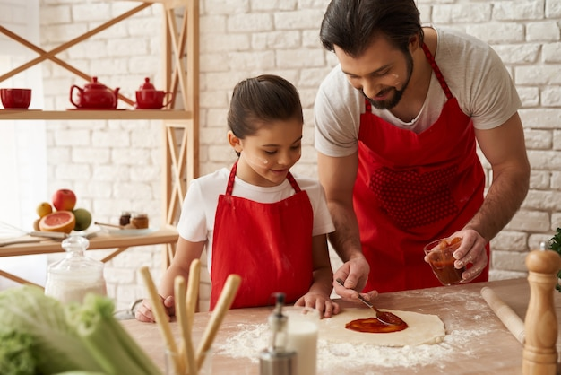 Dad and daughter prepare pizza with tomato sauce.