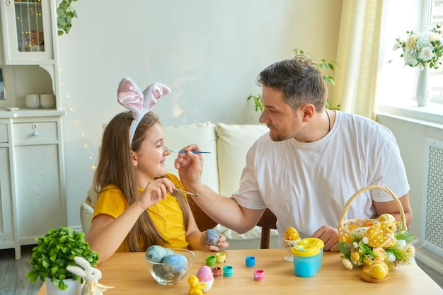 Dad and daughter stain each other's faces with blue paint for painting eggs. on the table is a basket with easter eggs and paints.